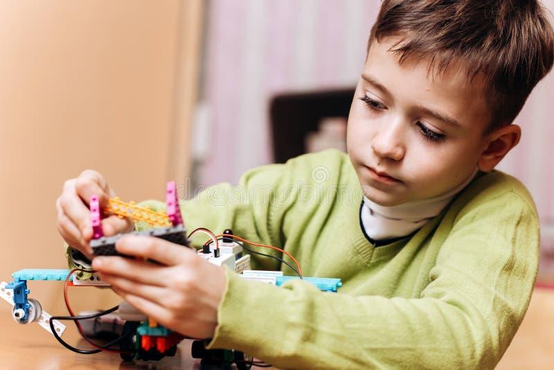 El muchacho diligente vestido en suéter verde se sienta en el escritorio con el ordenador y hace el robot del constructor robótic foto de archivo