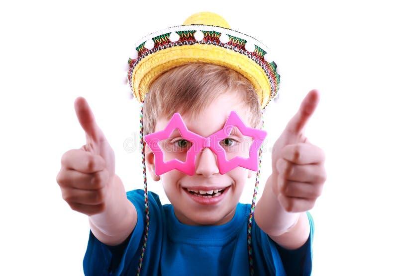 El muchacho divertido hermoso en una camiseta azul que lleva asteroide elegante colorido y los vidrios y sombrero amarillo del som foto de archivo libre de regalías