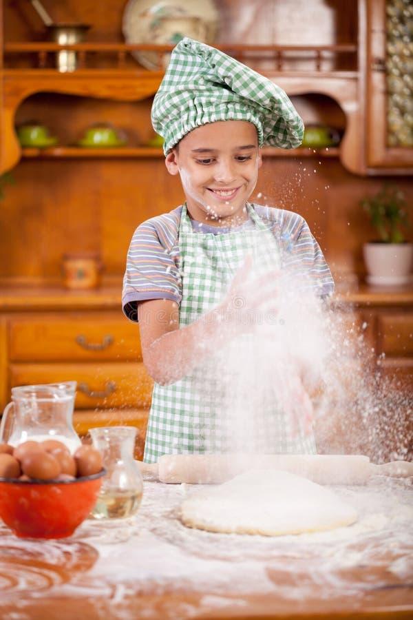 El muchacho divertido joven asperjó la harina sobre la pasta en la cocina imágenes de archivo libres de regalías