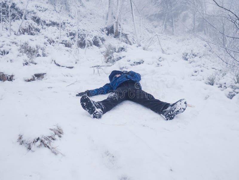 El muchacho divertido que pone en nieve y hace un ángel con los brazos separados El niño está jugando en nieve fotos de archivo libres de regalías