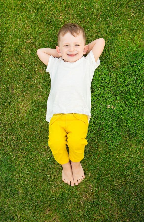 El muchacho divertido que tiene toma el sol la mentira en la hierba fotografía de archivo libre de regalías