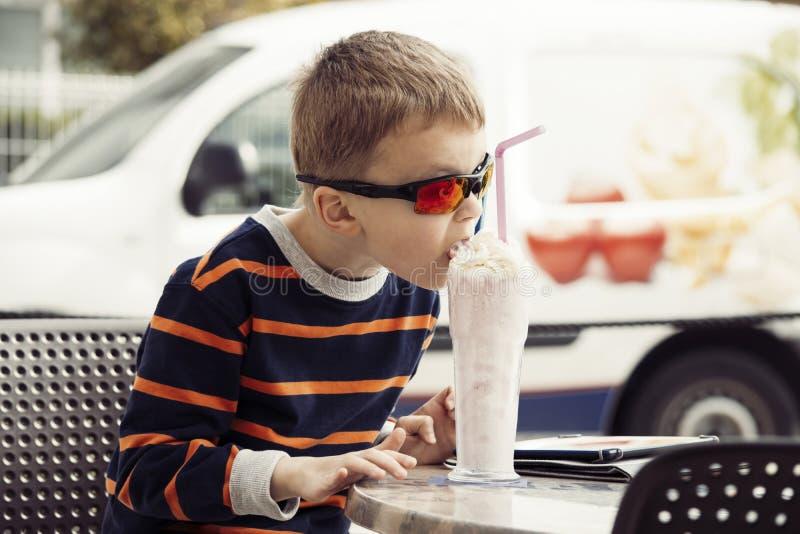 El muchacho elegante bebe un batido de leche con helado fotografía de archivo