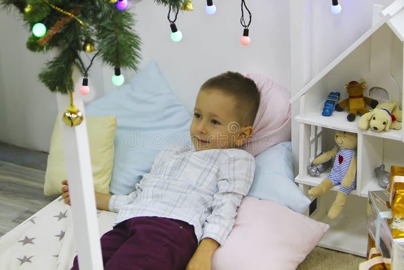 El muchacho elegante feliz está mintiendo en la cama cerca del árbol de navidad fotos de archivo