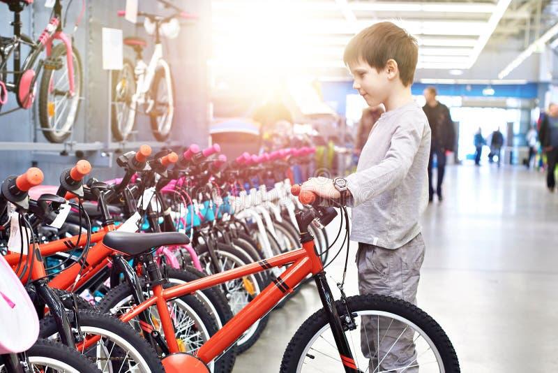 El muchacho elige la bicicleta en supermercado de los deportes foto de archivo libre de regalías