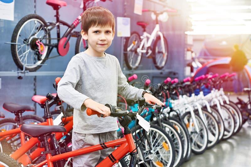 El muchacho elige la bicicleta en tienda del deporte foto de archivo