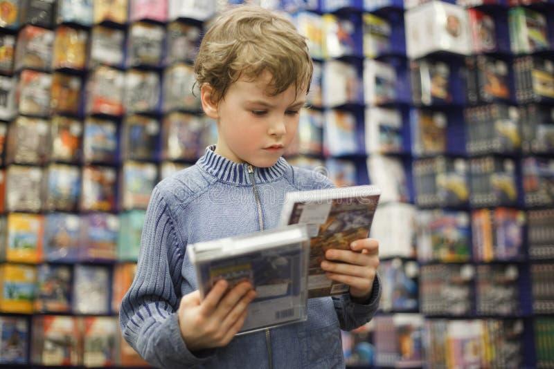 El muchacho elige uno del dvd dos en almacén especial fotos de archivo libres de regalías