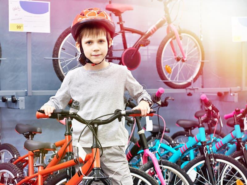 El muchacho en casco elige con la bicicleta en tienda del deporte imágenes de archivo libres de regalías