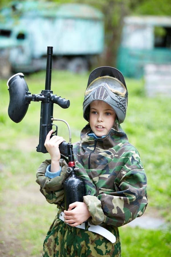 El muchacho en juego del camuflaje sostiene un arma del paintball imagen de archivo