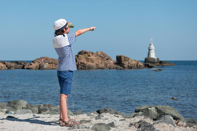 El muchacho en la camiseta rayada y un casquillo en la playa fotografía de archivo libre de regalías