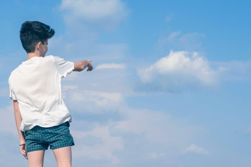 El muchacho en la camiseta y los pantalones cortos muestra su finger en el cielo azul y el avi?n de aterrizaje nublados Verano y  foto de archivo