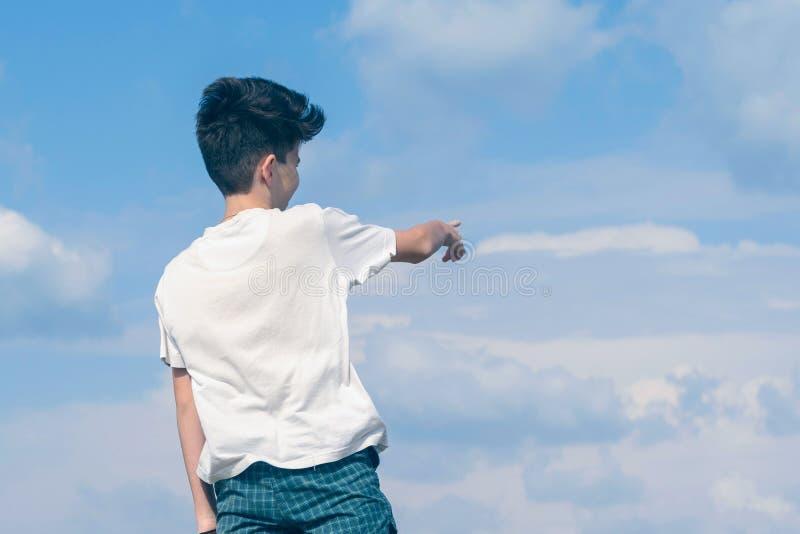 El muchacho en la camiseta y los pantalones cortos muestra su finger en el cielo azul nublado Verano y concepto del viaje imagenes de archivo