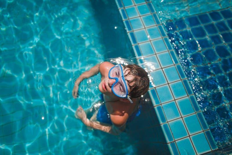 El muchacho en la máscara para nadar en la piscina con agua azul Él se relaja con los ojos cerrados En la máscara azul de la cara foto de archivo libre de regalías