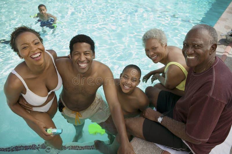 El muchacho (7-9) en la piscina con los padres y los abuelos elevó el retrato de la visión. imagenes de archivo