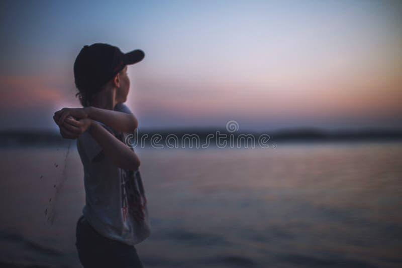 El muchacho en la playa lanza piedras en el agua fotografía de archivo