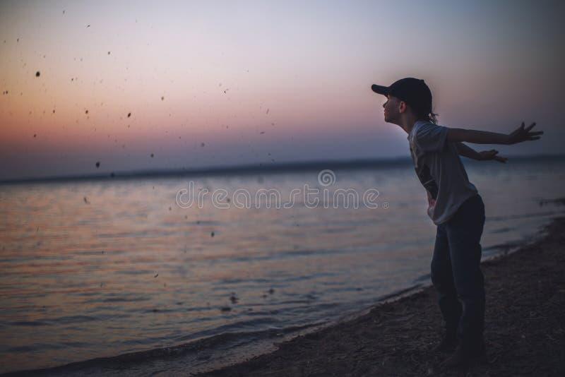 El muchacho en la playa lanza piedras en el agua fotos de archivo