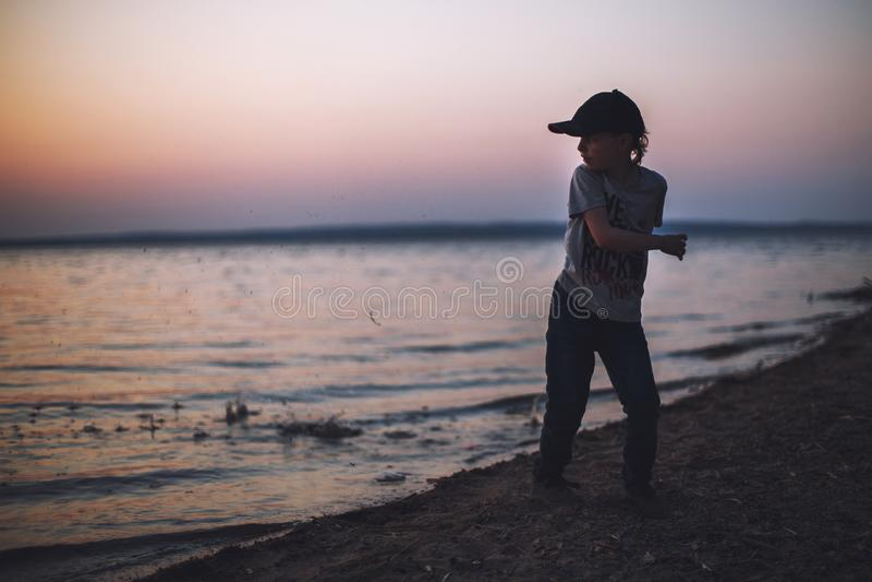 El muchacho en la playa lanza piedras en el agua imagen de archivo