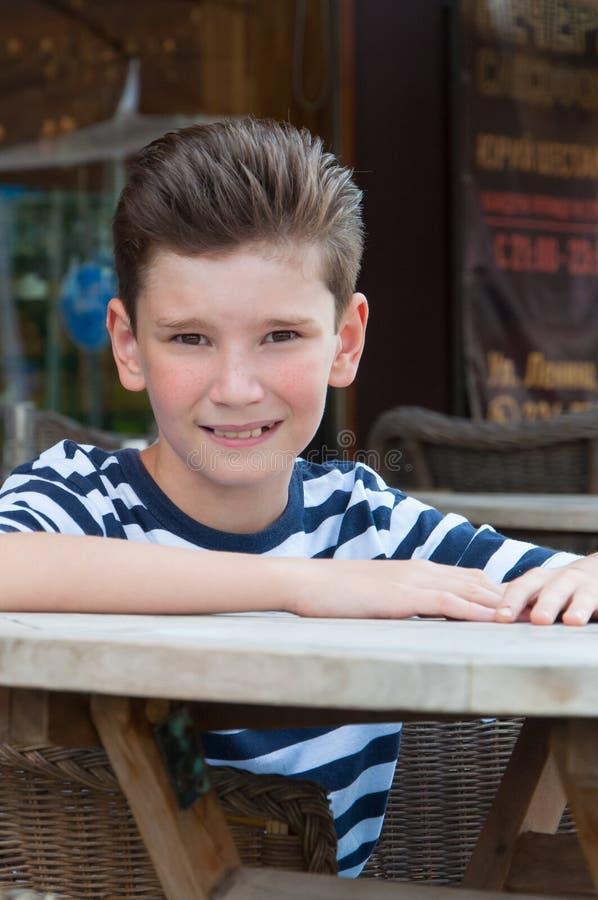 El muchacho en la tabla en un café de la calle El concepto: peinado de la moda foto de archivo libre de regalías