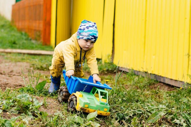 El muchacho en el traje amarillo que juega con un coche del juguete en la suciedad foto de archivo