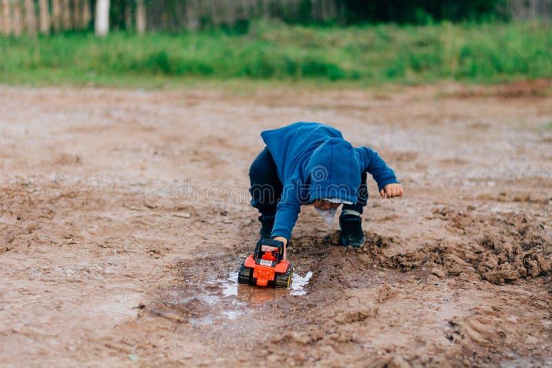 El muchacho en traje azul juega con un coche del juguete en la suciedad foto de archivo