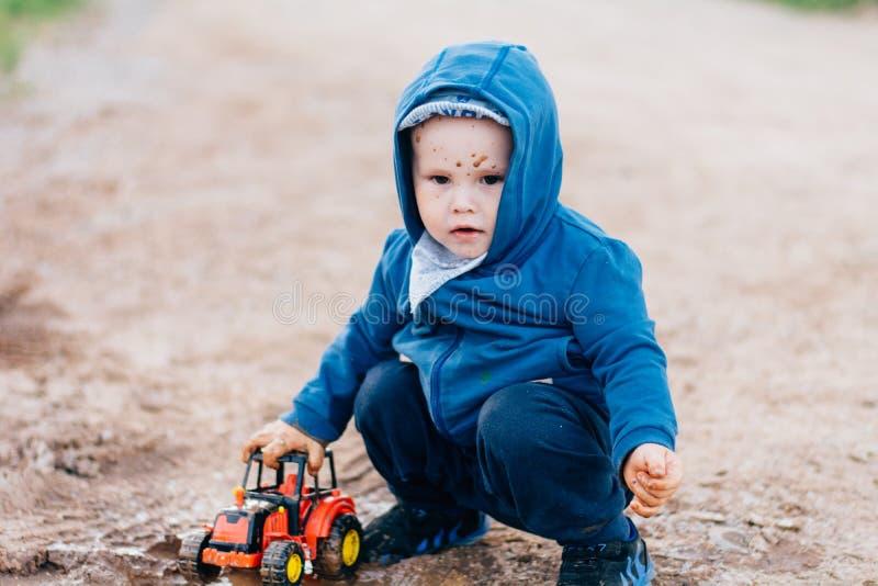El muchacho en traje azul juega con un coche del juguete en la suciedad fotografía de archivo libre de regalías