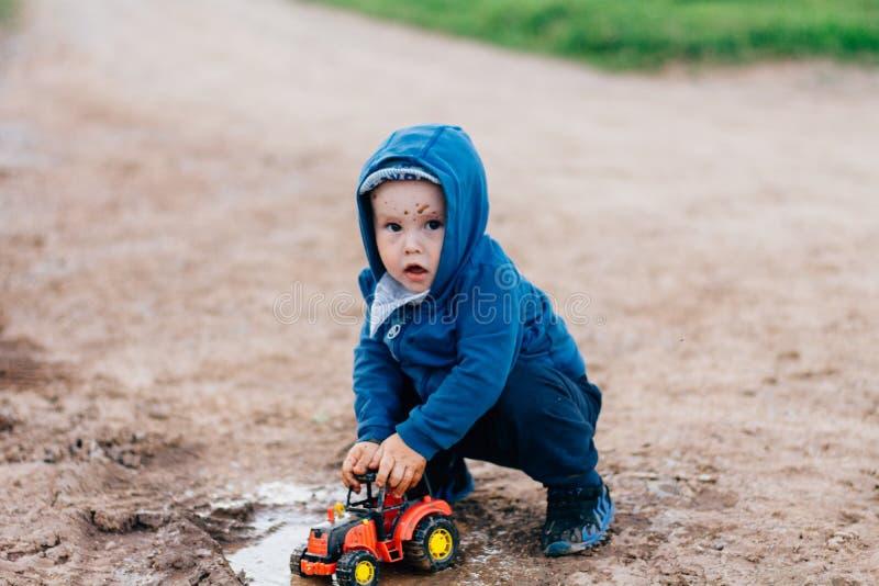 El muchacho en traje azul juega con un coche del juguete en la suciedad imágenes de archivo libres de regalías
