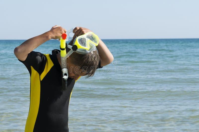 El muchacho en traje de salto saca su máscara y tubo respirador en el mar imágenes de archivo libres de regalías
