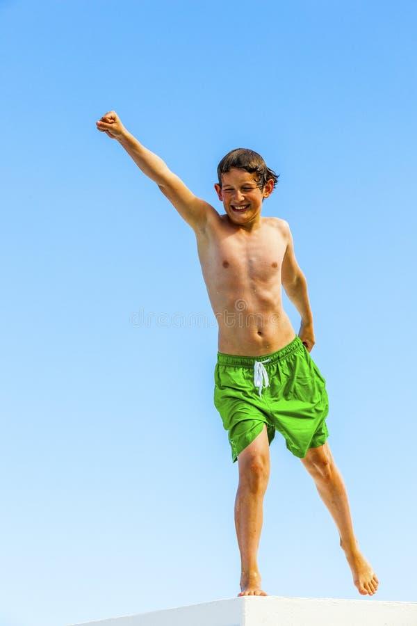 El muchacho en troncos de nadada pega una actitud fotos de archivo