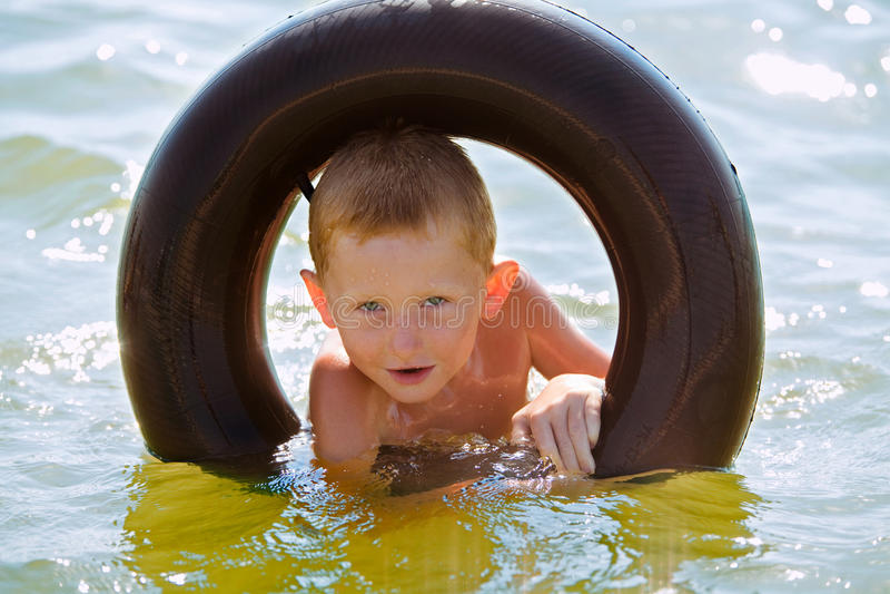 El muchacho en un anillo de goma fotos de archivo