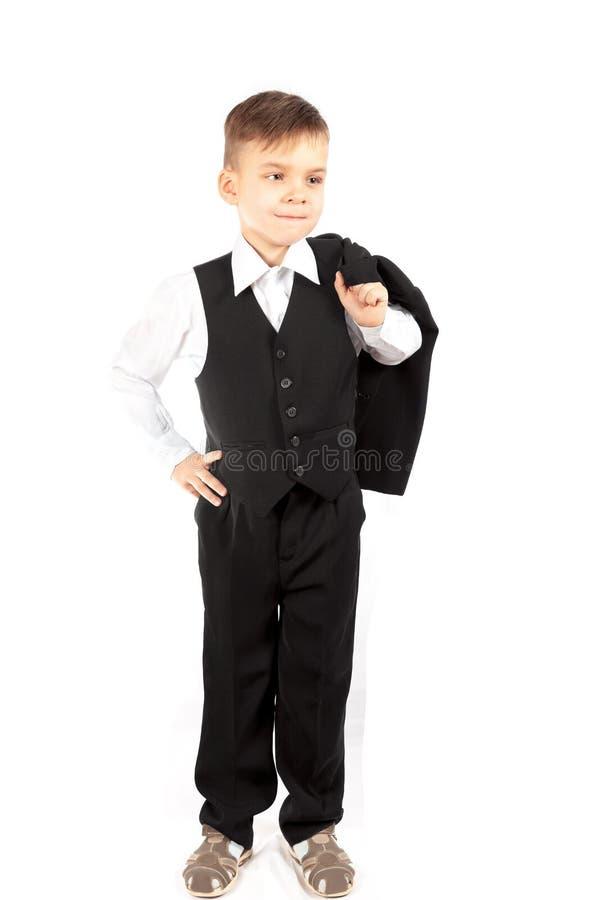 El muchacho en un chaleco y pantalones sostiene una chaqueta en su hombro imagenes de archivo