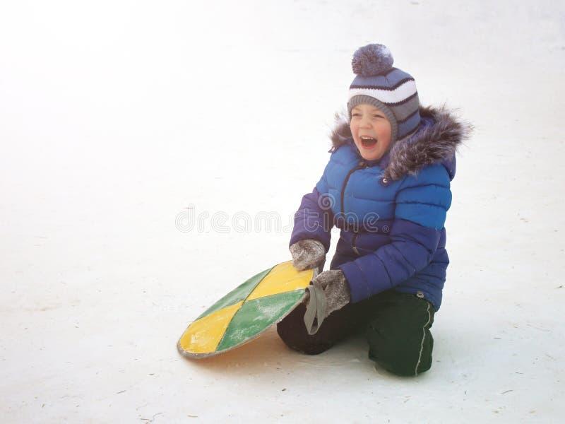El muchacho en un sombrero azul caliente está caminando afuera en el invierno imagen de archivo libre de regalías