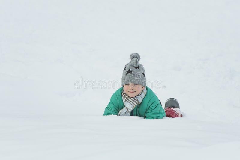 El muchacho en un sombrero, una bufanda y una chaqueta verde está mintiendo en la nieve en sus codos Retrato Día de invierno fotografía de archivo libre de regalías