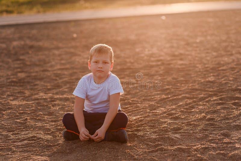 El muchacho en una camiseta blanca se sienta en la arena imagen de archivo libre de regalías
