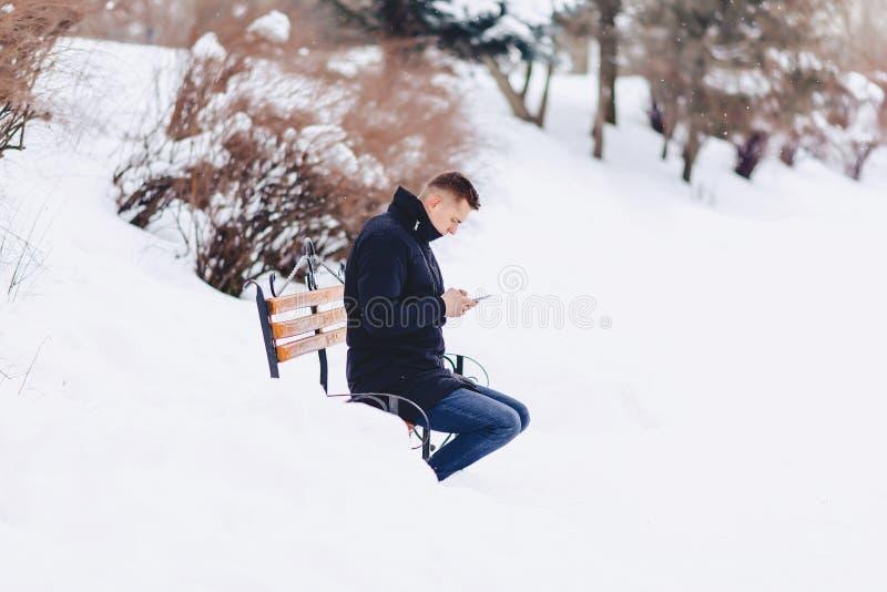 el muchacho en una chaqueta del invierno en un banco escribió SMS fotos de archivo