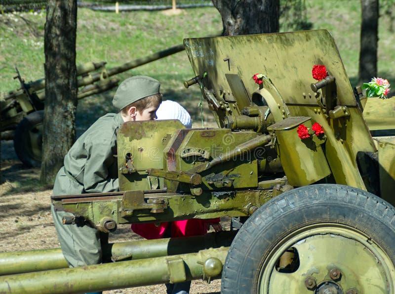 El muchacho en uniforme militar mira con alcance del actual arma divisional histórico fotos de archivo