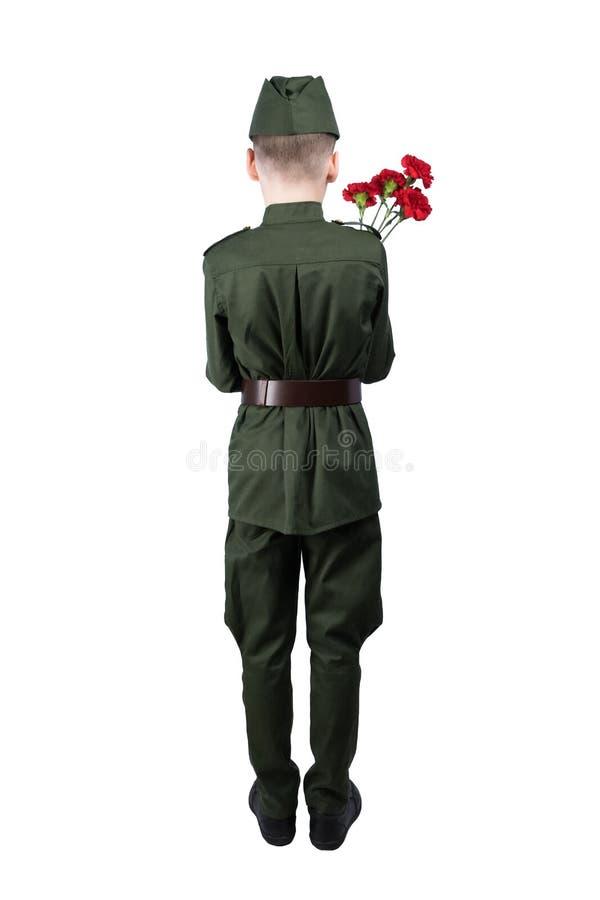 El muchacho en uniforme militar se está colocando con el suyo detrás dado vuelta y está sosteniendo las flores rojas para felicit fotos de archivo