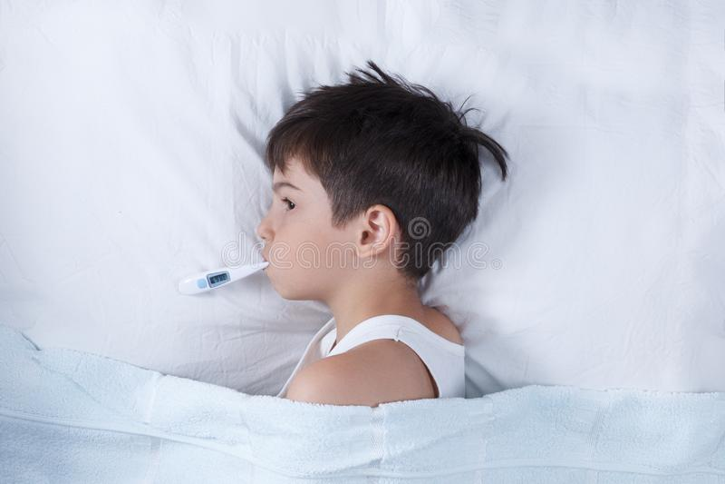 El muchacho enfermo, el niño con el termómetro en una boca, en una cama, el concepto de una enfermedad foto de archivo libre de regalías