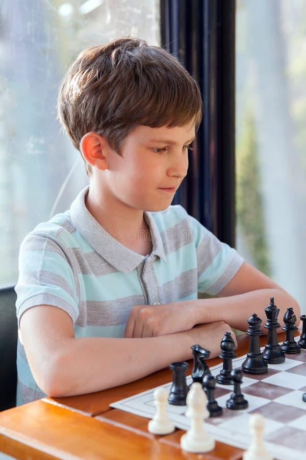 El muchacho enfocado está jugando en ajedrez imagen de archivo
