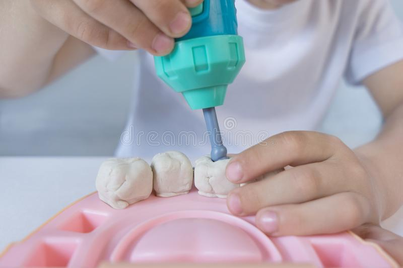 El muchacho es 5 años y juegos en la colección del Dr. y boro dental de los rellenos de los taladros en los dientes de la arcilla imágenes de archivo libres de regalías