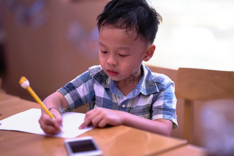 El muchacho es papel de escribir con el lápiz y el teléfono elegante de los padres en la tabla fotos de archivo libres de regalías