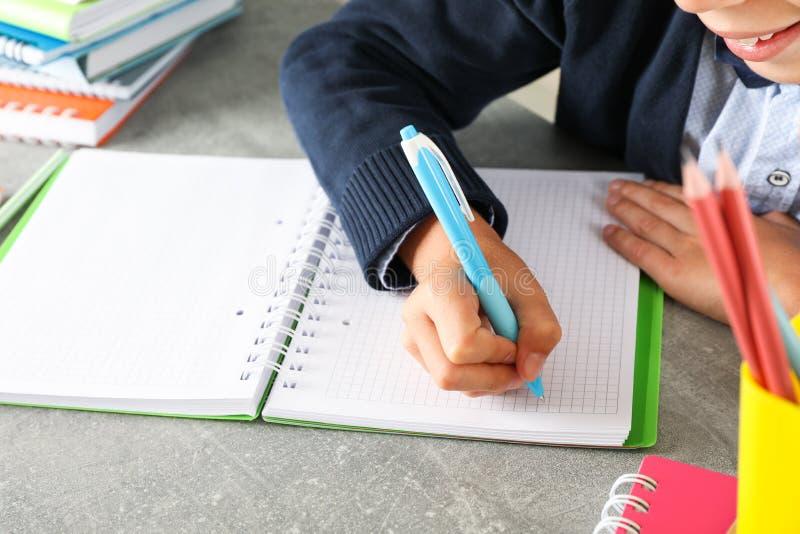 El muchacho escribe en un cuaderno en la tabla gris imagenes de archivo