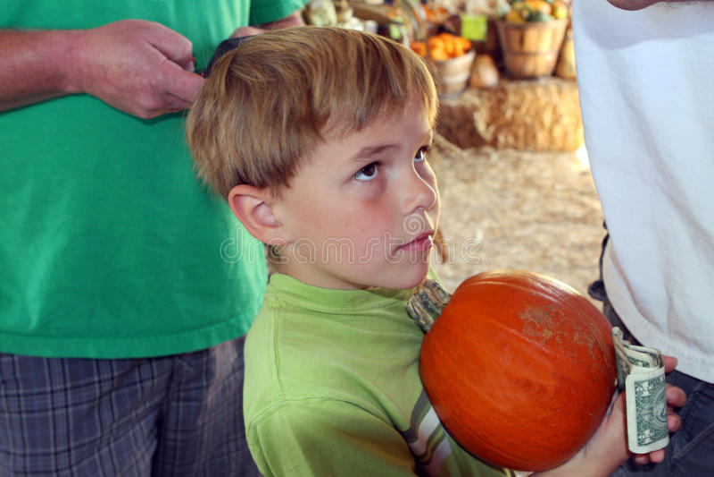 El muchacho espera en línea para comprar la calabaza imágenes de archivo libres de regalías