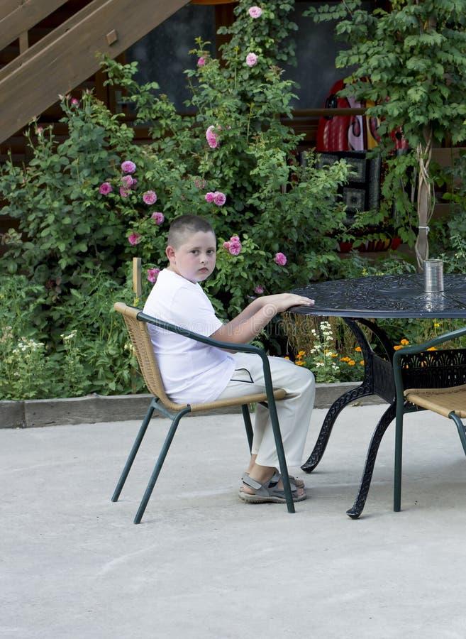 El muchacho espera un desayuno en una tabla en el aire abierto imagenes de archivo