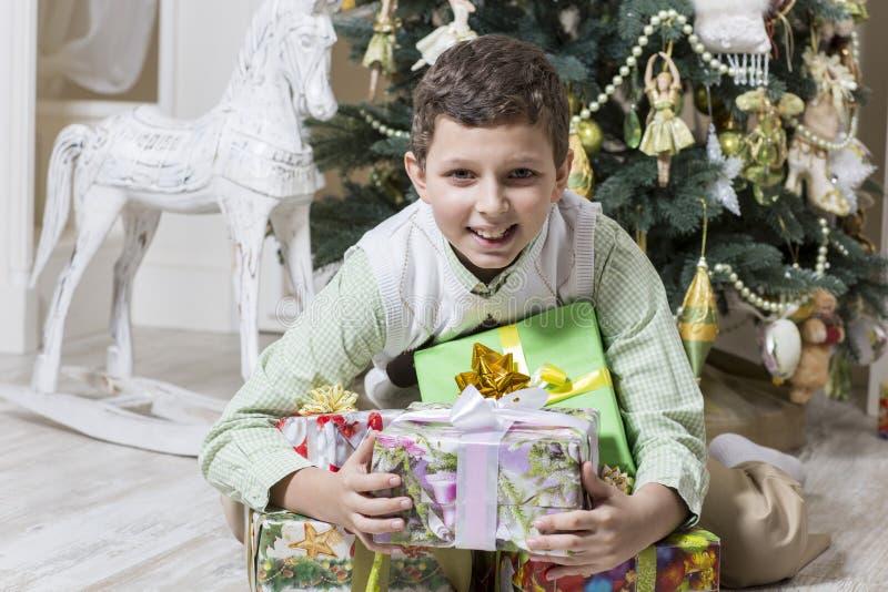 El muchacho está abrazando los regalos de la Navidad imagen de archivo