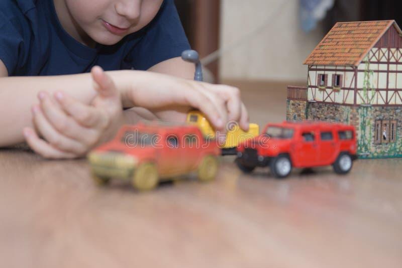 El muchacho está jugando los coches del juguete fotografía de archivo libre de regalías
