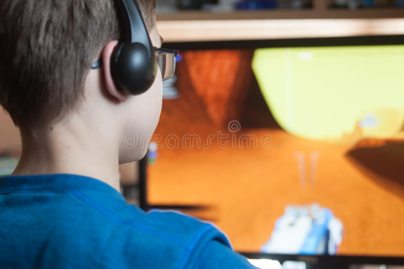 El muchacho está jugando a un juego de ordenador foto de archivo