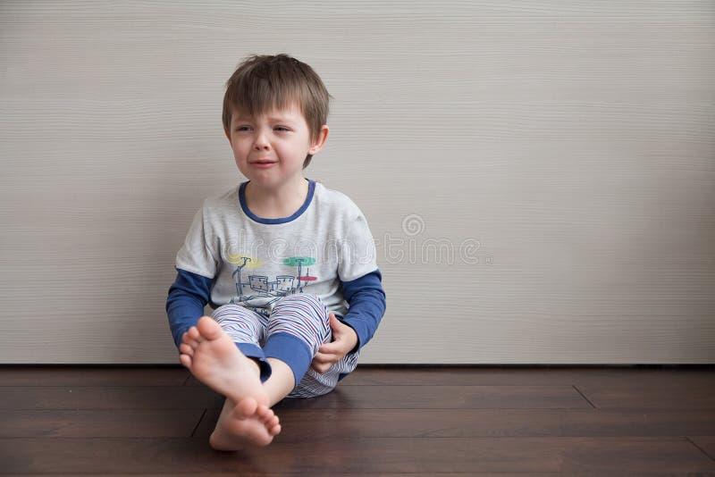 El muchacho está llorando El niño se está sentando en el piso imagen de archivo