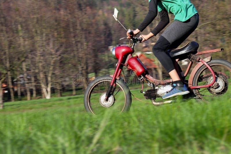 El muchacho est? montando en la moto en campo Motocicleta roja especial despu?s de que la renovaci?n est? como nueva Jawa 50 del  fotografía de archivo