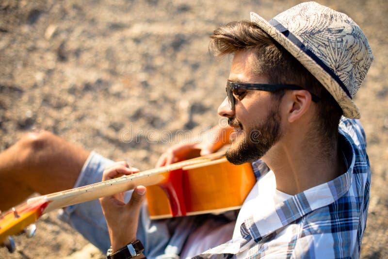 El muchacho está tocando la guitarra en la playa foto de archivo