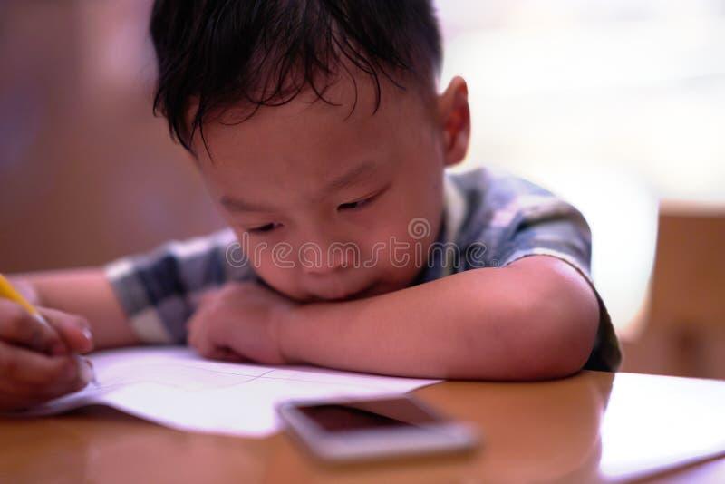 El muchacho está trabajando en la preparación en la tabla foto de archivo