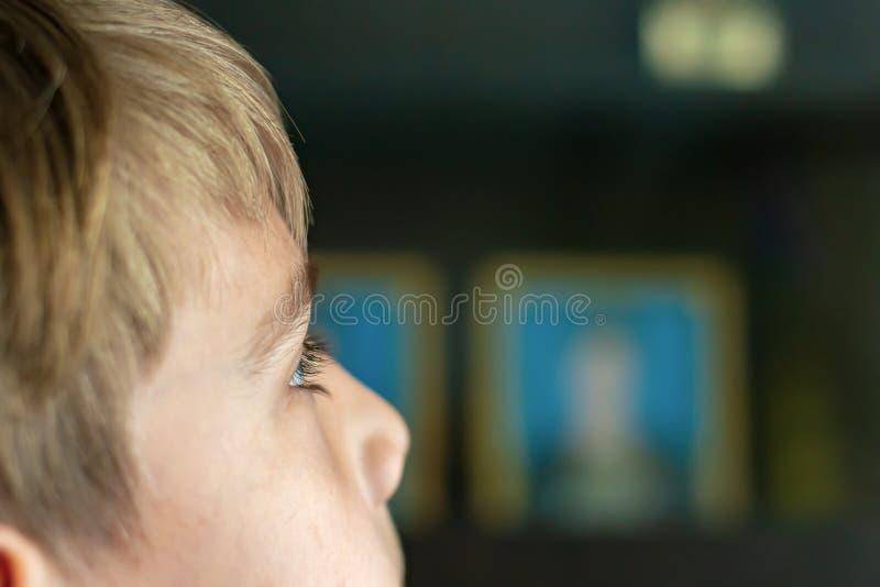 El muchacho está viendo la TV, los ojos del niño está cercano para arriba, contra la perspectiva de una televisión de trabajo fotografía de archivo